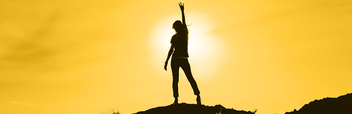 student standing on a mountain top in the sunset